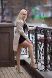 有完善的腿的女孩在城市广场的裤袜 免版税库存照片