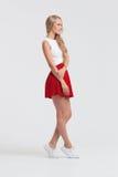 有完善的身体的女孩在白色背景的红色裙子 库存照片