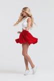 有完善的身体的女孩在白色背景的红色裙子 免版税库存图片