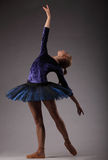 有完善的身体的美丽的芭蕾舞女演员在蓝色芭蕾舞短裙成套装备跳舞在演播室 库存图片