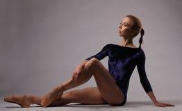 有完善的身体的芭蕾舞女演员在蓝色成套装备在演播室 库存图片