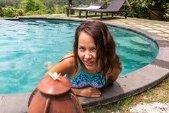 有完善的身体的迷人,性感和热的白肤金发的女孩,在泳装,摆在游泳池 免版税库存照片