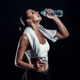 有完善的身体饮用水的可爱的运动少妇从有毛巾的一个瓶在她的反对黑背景的脖子上 免版税库存照片