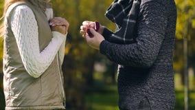 有定婚戒指的要求的人妇女与他结婚在秋天公园,惊奇 库存照片