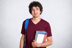 有宜人的迷人的微笑的,举行正面年轻男性少年预定,运载袋子,为类做准备在学院,喜欢studyi 库存照片