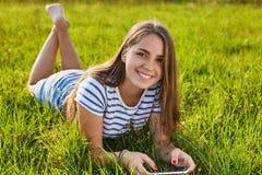 有宜人的说谎和放松在草的微笑和黑暗的长的头发的一个可爱的女孩在她的手上拿着她的智能手机 照相机爬行的metallica p塔兰图拉毒蛛往 免版税库存照片