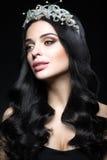 有宝石、卷毛和晚上构成冠的美丽的深色头发的妇女  秀丽表面 免版税库存图片