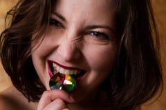 有宝石的年轻美丽的深色的女孩在她的嘴 库存照片