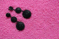 有宝石的黑耳环在背景桃红色小珠 免版税库存照片