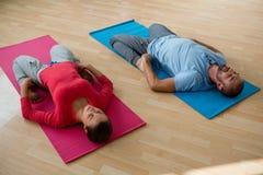 有实践斜倚的英雄姿势的学生的辅导员在瑜伽演播室 免版税库存照片