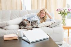 有宠物猫的愉快的金发碧眼的女人在沙发 库存照片