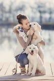 有宠物的美丽的女孩在湖附近 免版税库存图片