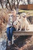 有宠物的美丽的女孩在湖附近 免版税图库摄影