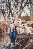有宠物的美丽的女孩在湖附近 免版税库存照片