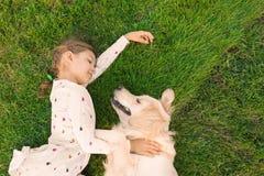有宠物的逗人喜爱的小孩在绿草,顶视图 图库摄影