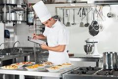 有审阅烹调的剪贴板的厨师 免版税库存照片