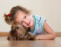 有室内约克夏狗的逗人喜爱的小女孩 库存照片