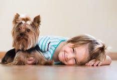 有室内约克夏狗的逗人喜爱的小女孩 免版税库存照片