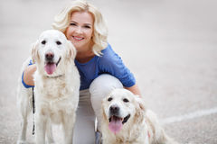 有室外两只金黄的拉布拉多猎犬的白肤金发的妇女 免版税图库摄影