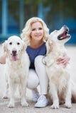 有室外两只金黄的拉布拉多猎犬的白肤金发的妇女 免版税库存照片