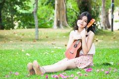 有室外尤克里里琴的吉他的亚裔女孩 免版税库存照片