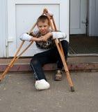 有室外断腿和木的拐杖的疲乏的男孩 免版税库存图片