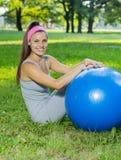 有室外普拉提的球的健身健康少妇 免版税库存照片