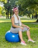 有室外普拉提的球的健身健康少妇 库存照片