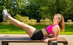 有室外桃红色顶面的锻炼的少妇运动的女孩 免版税库存照片