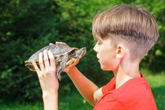 有室外的乌龟的青少年的男孩 库存照片