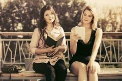 有室外的书和数字式片剂的计算机的两名年轻时尚妇女 库存图片