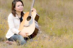 有室外的吉他的愉快的妇女 免版税库存照片