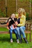 有室外的女儿和的猫的母亲 图库摄影