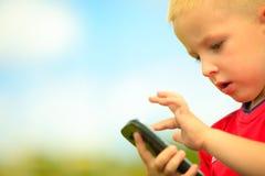 有室外的手机的小男孩 技术一代 免版税库存图片
