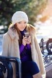 有室外的杯子的美丽的愉快的微笑的冬天妇女 免版税库存照片