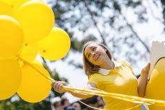 有室外的气球的愉快的微笑的妇女 免版税库存照片