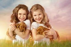 有室外红色的小狗的逗人喜爱的两个小女孩 孩子宠物友谊 免版税库存照片