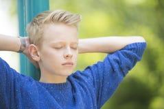 有室外闭合的眼睛的轻松的少年男孩 免版税库存图片