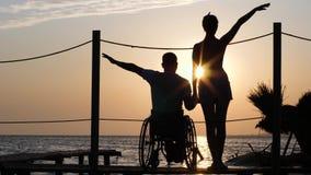 有害病的腿的人在有女朋友的轮椅反对日落背景的浪漫旅行的在明亮的射线的 股票视频