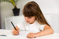 有家庭作业的女孩 免版税库存图片