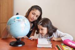 有家庭作业的母亲帮助的女儿 免版税库存照片