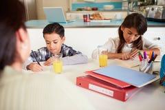 有家庭作业的母亲帮助的孩子在表上 免版税库存图片
