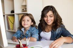 有家庭作业的母亲帮助的孩子 图库摄影