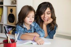 有家庭作业的母亲帮助的孩子 免版税库存图片