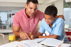 有家庭作业的父亲帮助的儿子 免版税库存照片