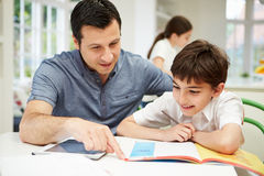 有家庭作业的父亲帮助的儿子 库存图片
