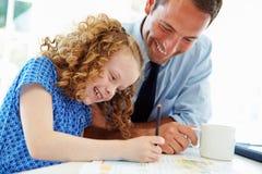 有家庭作业的父亲帮助的女儿在厨房里 库存照片