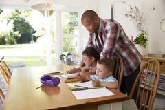有家庭作业的父亲帮助的孩子在表上 免版税库存照片