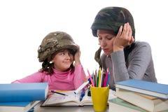 有家庭作业任务的母亲帮助的女儿 免版税库存图片