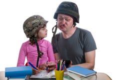 有家庭作业任务的父亲帮助的女儿 库存照片